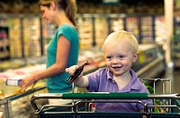 Toddler boy playing with toy in shopping cart