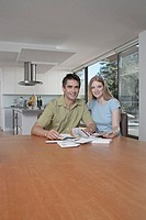 Man and woman reading papers in kitchen
