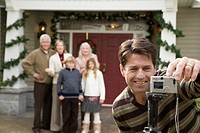 Man adjusting camera to take family portrait