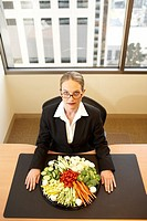 Businesswoman with tray of vegetables