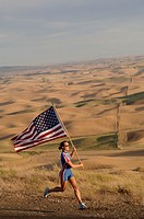 Female athlete with American flag on roadside