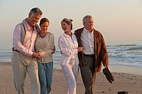 Mature couples walking on the beach