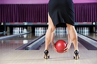Woman in high heels bending to throw bowling ball