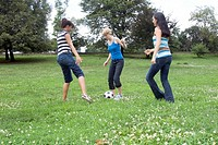 Three teenage girls playing with soccer ball outdoors