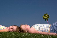 Young girls relaxing in grass outdoors