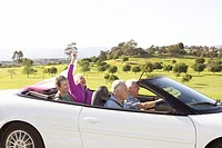 Senior couples driving in white convertible
