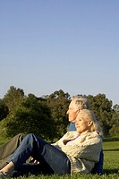 Senior couple relaxing in meadow