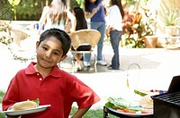 Young Hispanic boy holding plate of food