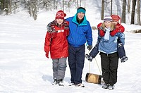 Family pulling sled up snowy hill