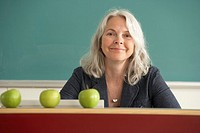 Teacher sitting behind desk with apples