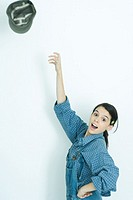 Teenage girl throwing hat into air, portrait