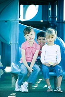 Children sitting on end of slide, smiling at camera