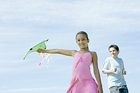 Girl holding out kite, boy in background