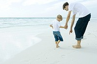 Man and son on beach, man pointing to sand