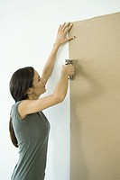 Woman stapling sheet of cardboard to wall