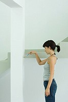 Woman painting wall with paint brush