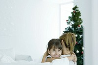 Girl hugging mother by Christmas tree