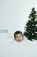 Boy looking over edge of couch, smiling at camera, Christmas tree in background