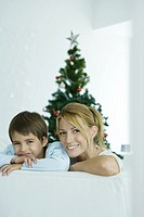 Woman and son sitting on couch in front of Christmas tree