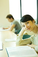 Female college student sitting at table with book, smiling at camera