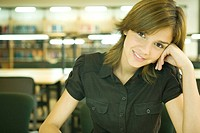 Female college student in library, smiling at camera
