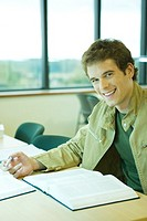 Male college student sitting in library, smiling at camera