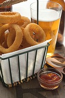 Deep-fried onion rings in wire basket, ketchup, beer, salt