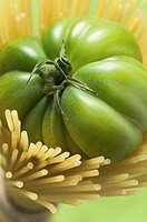 Green beefsteak tomato in a bundle of spaghetti
