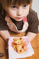Child holding freshly-baked puff pastries on cloth