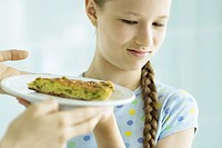 Girl making face at piece of quiche