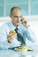 Man sitting at table eating hamburgers, reading newspaper and using cell phone