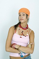 Teen girl wearing lots of accessories, arms folded, looking at camera, portrait