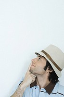 Young man wearing hat, finger over lips, looking up