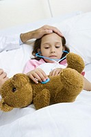 Child holding toy stethoscope to teddy bear, doctor feeling child´s forehead