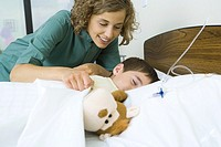 Boy lying in hospital bed asleep, nurse covering boy with blanket