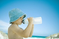 Child drinking water on beach