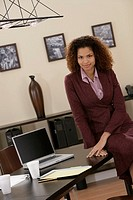 Business woman sitting on a desk