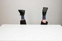 Anonymous office worker fallen over behind an empty desk.