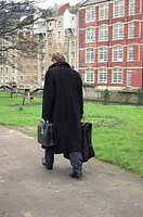 Young businessman walking with briefcase and overnight bag