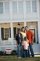 Family standing in front of new house