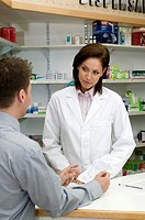Young female pharmacist with customer, close-up