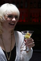 Young woman holding martini in nightclub, laughing, looking away