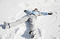 Young woman making snow angel, smiling, elevated view