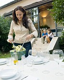 Mother mixing salad on garden table, children in background