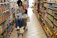 Young couple in supermarket, man sitting in trolley, smiling