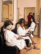 Women sitting under dryer at hairdressers
