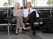Mature businessman and woman sitting in airport lounge
