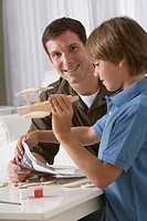 Father building model airplane with his son