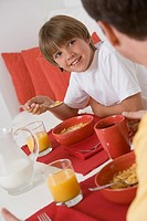 Boy eating breakfast with his father