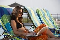 Woman using laptop at poolside